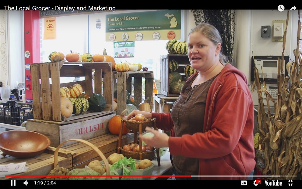Screen capture of a video showing a woman demonstrating how to display vegetables for sale